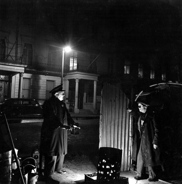 29 March 1952  Bill Howard a Romany night watchman in Belgrave Square, talking to Fred Evans chauffeur to the Saudi Arabian Ambassador and ex chaffeur to the Duke of Alba  Belgravia, London, England - gypsy roma gipsy 1950s 50s fifties working man
