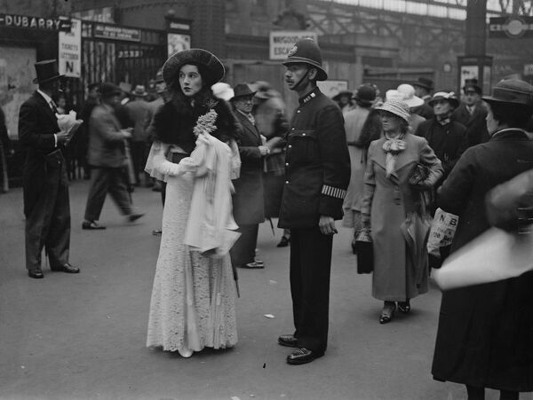 Asking a policeman at Waterloo.  Mrs Challenor Lynch asking a policeman for the correct train for Ascot and the races at Waterloo Station.  20 June 1935