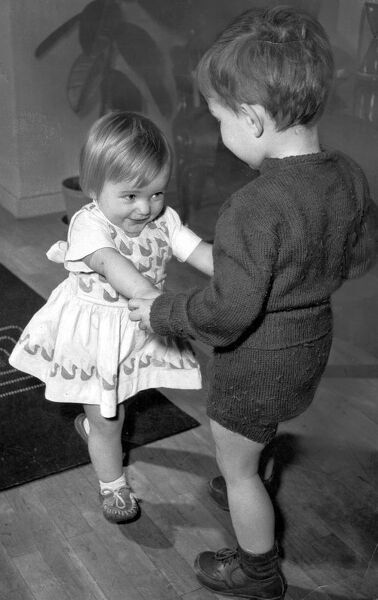 Boy and girl toddlers playing together dancing partners dance / dancing / party season / celebration / happy vintage news archive