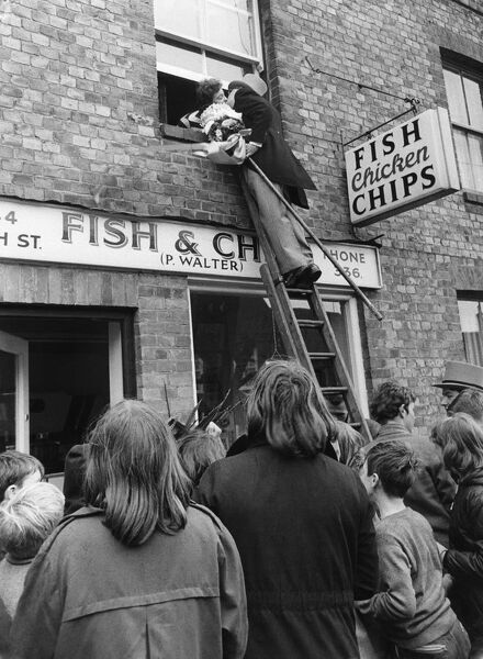 The bridegroom climbs a ladder to kiss his bride at the window above a fish and chip shop. love couple romance romantic for valentines day be my valentine