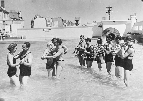 Brussels is now sweltering in a heatwave, bathers may perform Foxtrots and other dances in the water to the music of a band in bathing costumes.  18 August 1937.    love couple romance romantic for valentines day be my valentine