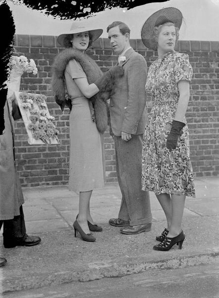 Buttonhole for Lord's.  Miss Betty Archer, one of the famous Society twins, pins a carnation in her brother's buttonhole when they arrived at Lord's ground for the second day of the Eton and Harrow match