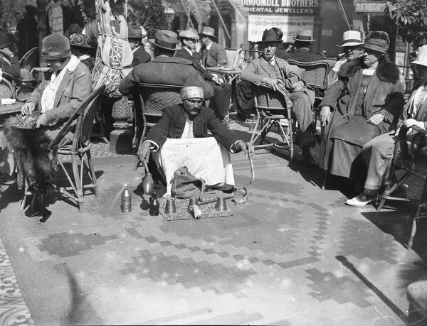 The Cairo Season.  The native conjurer entertaining guests on the terrace at the Shepheard Hotel.   February 1925
