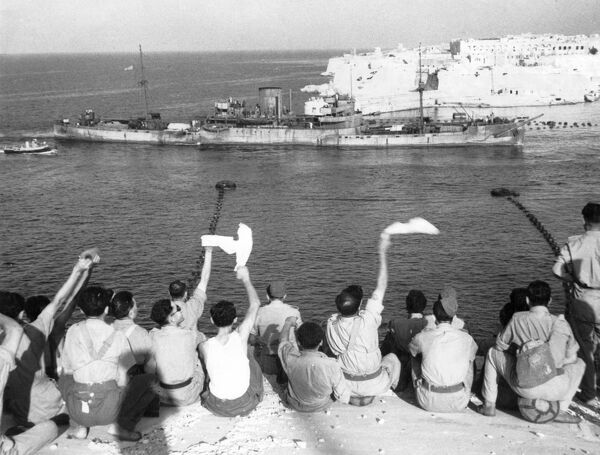 The convoy entering the harbour. Troops wave and cheer as more boats of the convoy arrive in Malta (ship probably City of Rochester)