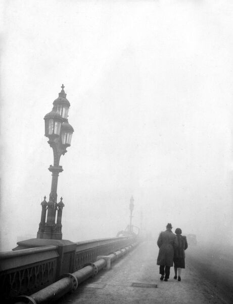 Couple walking across a bridge in London in fog  1950s love couple romance romantic for valentines day be my valentine