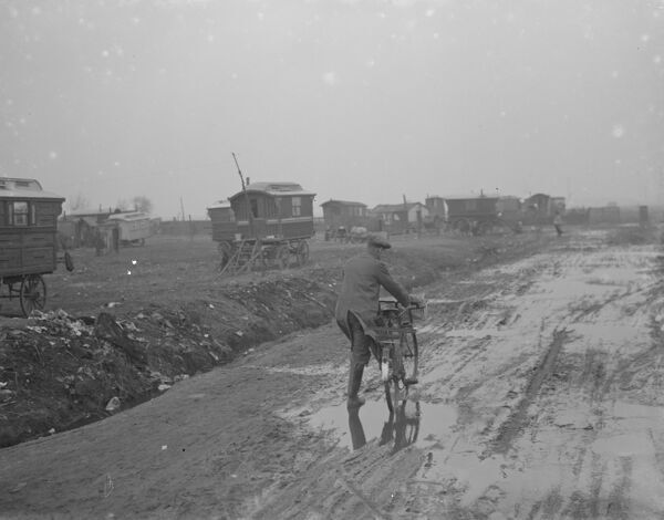 A cyclist negotiates a very muddy road with gypsy caravans parked on Belvedere marshes .  1936 Travellers Romany Gypsy Gipsy gypsies Roma. social history