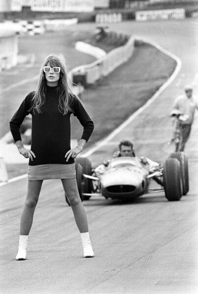 "Dangerous corner.....  Brands Hatch, Kent, England ; Unidentified speed car driver negotiates what appears to be a "" dangerous corner "" at the Brands Hatch motor circuit here today. The girl on the track is 22 year old French idol"