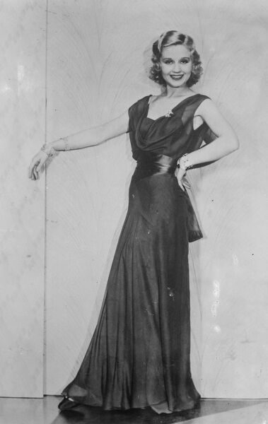 Draped neckline for evening wear.   Beautiful Adrrenne Lore wearing a gown of double chiffon in royal blue, with a draped neckline and a wide sash of matching satin.   16 April 1932