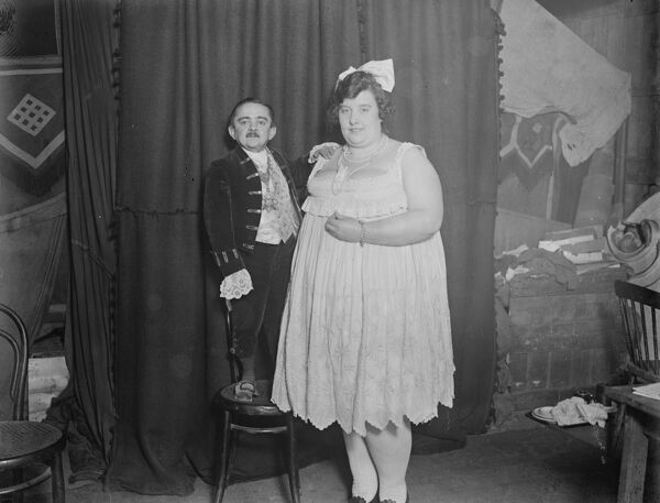 Dwarf marries the fat lady.  World 's Fair showmen at the Agricultural Hall celebrated the wedding of Mr Robert Goudin, the dwarf and Miss Ruby Trixy one of the ' fat ladies ' at the fair. The bridegroom 41 years of age, weighs 3 stone and is only 3 ft high