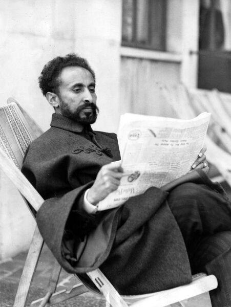 Emperor Haile Selassie I of Abyssinia is enjoying a seaside holiday at Eastbourne, Sussex.  The Emperor of Abyssinia keeping in touch with the news of the day at Eastbourne.  18 July 1938