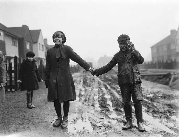 Fen Grove road complaint.  A young boy enjoys the mud.  1937