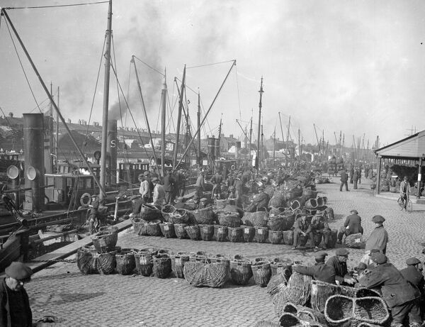 Herring Fishery at Great Yarmouth , Norfolk , England   The quayside with the steam drifters moored at the fish wharf and men waiting to unload the cargos .   1923