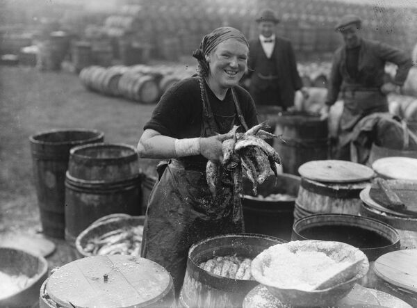 Herring harvest at Lowestoft  Scotch fisher girls gutting and packing the fish on the quay side Lowestoft .  6 November 1920 Fish where the fish are