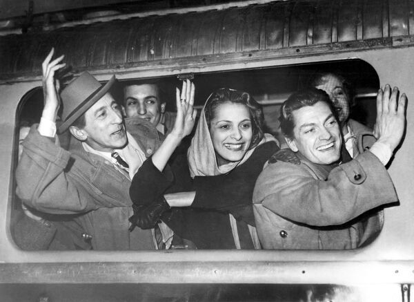 Jean Cocteau, the famous playwright-producer (left); Andree Debar, actress (centre), and Jean Marais, screen and stage actor, waving goodbye to friends as the train pulls out from Gare de Lyon to Marseilles. The Cocteau company will tour in Egypt
