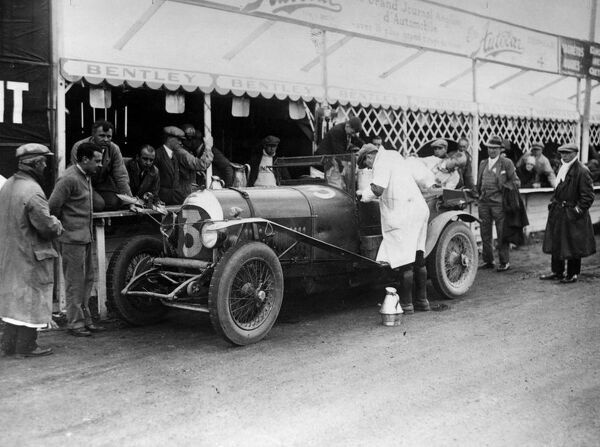 Le Mans 1927 Old Number 7 3 litre Bentley at the pits being refilled by Dr J D Benjafield while R A Clarke kneeling and W O Bentley next to him and Sammy Davis in crash helmet standing