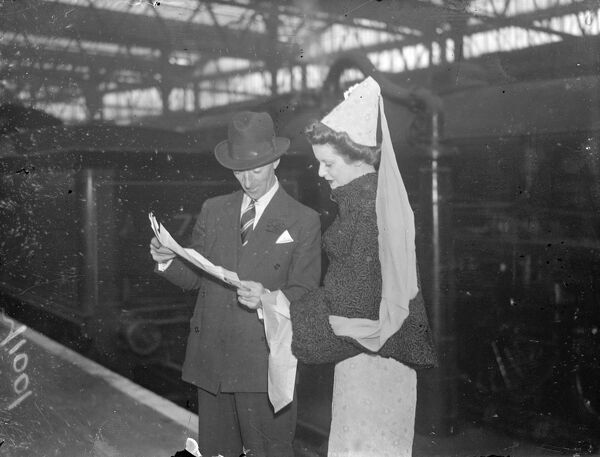 Medieval hat fashion.  Miss M Peters in an attractive hat fashion of 'mediaeval'style at Waterloo station, London, when passengers left on the 'Queen Mary'boat train for America.  10 November 1937