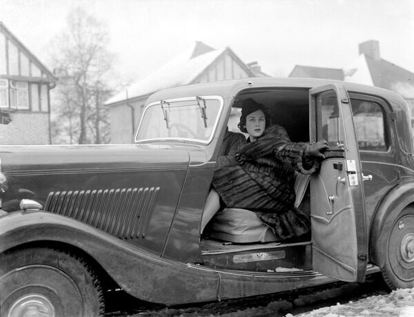 Miss Muriel Oxford sitting in the passenger seat of a car at the side of the road.  1937
