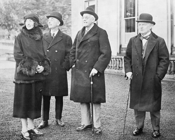 Mrs Lascelles, Sir Robert Horne, Lord Balfour and Mr Lloyd George in the grounds at Whittingham.  1923