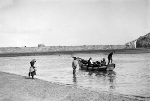 People out fishing from a Coble ( a locally made fishing boat ) at low tide, near the fishing town of Staithes, on the north east coast of England .  Early 1900s Fish where the fish are