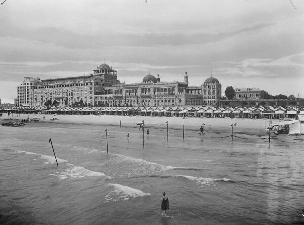 Queen of the Adriatic with thousands of English courtiers.   A fine new picture from the Lido, Venice, showing the bathing beach and the Excelsior Palace Hotel.  30 August 1928