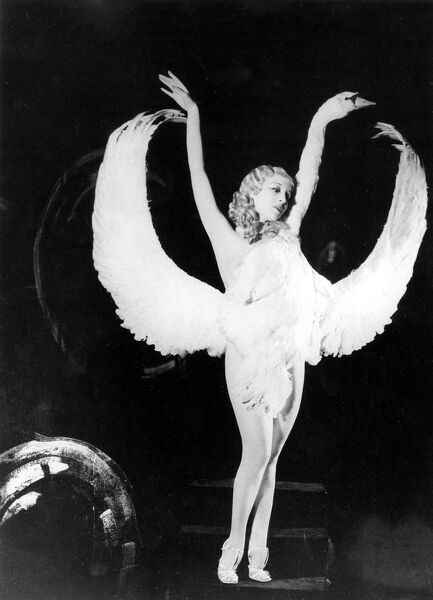 "Sally Rand of Fan Dance fame is shown in one of the positions in her new dance which she has named "" Leda and the Swan &quot"