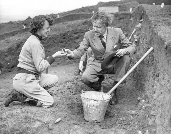 "Sir Mortimer Wheeler  Archaeologist and personality of TV programme ""Animal, Vegetable, Mineral ?"" pictured with Jean Webster at an excavation site on the Wye Downs, near Ashford, Kent.  25th August 1954"