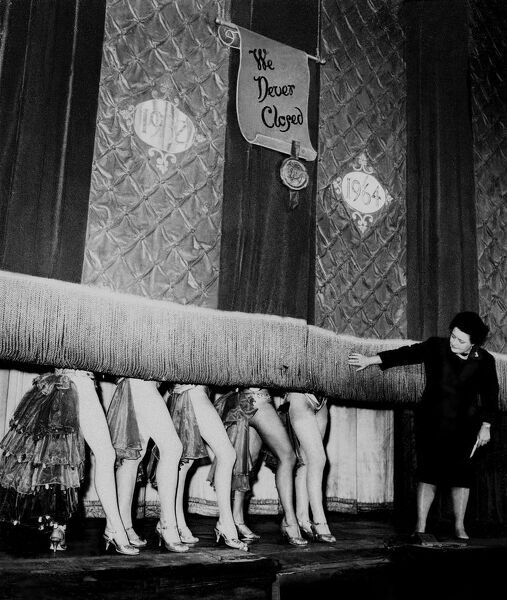 Windmill Theatre Owner Miss Sheila Van Dam watches as the curtain comes down over the legs of the Windmill Girl Dancers for the last time today as the era of the famous Windmill Theatre London comes to a close