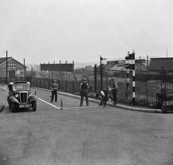 Workmen paint road markings on the road by some traffic lights in Swanley.  1936