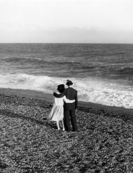 Young couple with their arms round each other enjoing the seaside. love couple romance romantic for valentines day be my valentine