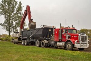 A 6x4 red Kenworth atic unit with a twin axle tipping trailer being loaded at Sudbury