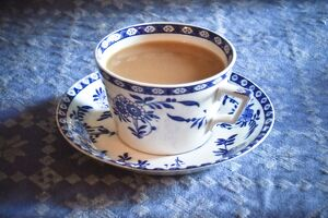 Antique blue and white cup and saucer of Indian tea with milk, on blue tablecloth