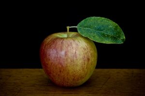 Apple with leaf on wooden surface against black background credit: Marie-Louise