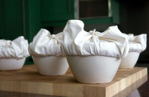 A batch of traditional English Christmas puddings, with cloths tied ready to steam