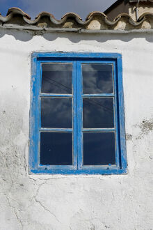 Blue framed window in white wall of Greek Cypriot house credit: Marie-Louise Avery
