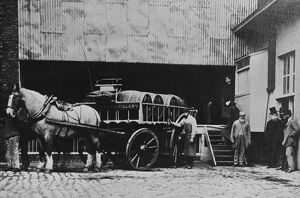 Brewery workers with a brewer's dray take a break from work for a portrait at the