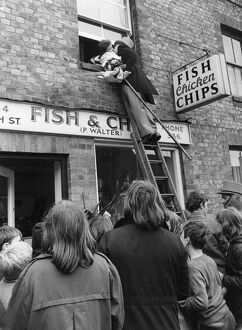 The bridegroom climbs a ladder to kiss his bride at the window above a fish and chip shop