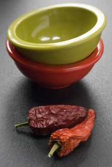 Two bright melamine bowls stacked on dark surface with two red hot chilli peppers