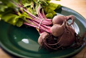 A bunch of freshly dug, whole beetroot on dark green plate. credit: Marie-Louise
