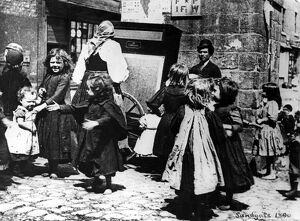 Children dance in the street to an organ grinder