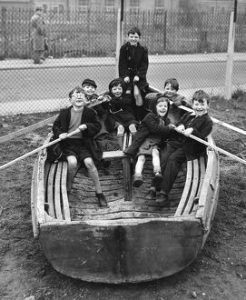 Children playing in an old boat in the Triangle Adventure Playground converted