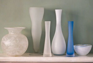 A collection of ground glass vases on mantel shelf, against, green wall credit