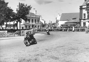 Competitors passing Ramsay Town Square at speed. Number 69 is W. J. Evans on AJS