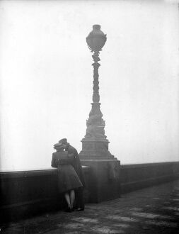 Couple arm in arm leaning over bridge in London in fog 1940s love couple romance