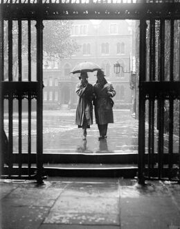 A couple walking in the rain under an umbrella in Deans Yard, Westminster Abbey