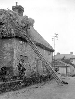 The craft of thatching - The thatcher at work on a picturesque Cottage at Amberley, Sussex