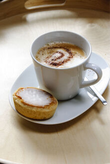 Cup of cappuccino with spiral of cocoa dusted on top with Swedish almond tart credit