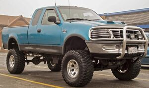 A customized Ford F150 with big wheels and tyres outside a Dairy Queen ' fast food