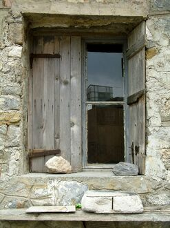 Deep set window in stone building with old weathered shutters held in place with a rock