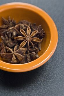 Dried Star anise fruits in small bowl. Also known as star aniseed, badiane or Chinese