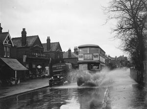 Flooded streets in Sidcup, Kent. Double dekker bus plows through the water